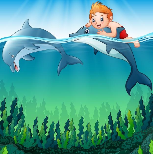 Niño De Dibujos Animados Con Delfines En El Mar Vector Premium