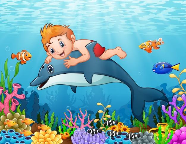 Niño De Dibujos Animados Con Natación De Delfines Vector Premium