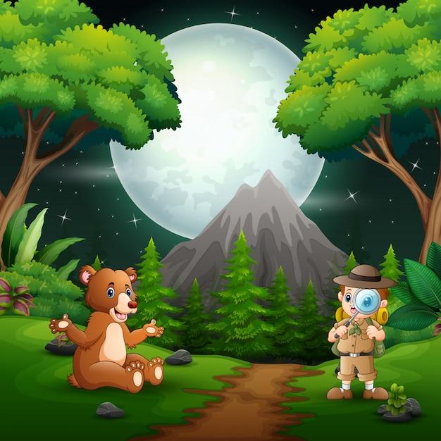 Niño explorador con un oso en la escena nocturna. Vector Premium