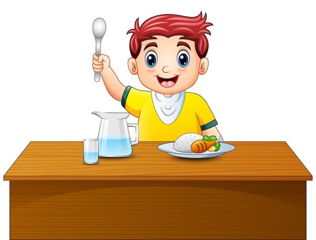 Niño Feliz De Dibujos Animados Con Cuchara En La Mesa De Comedor