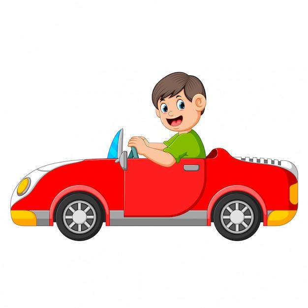 El niño está manejando el auto rojo con la buena posando. | Vector Premium