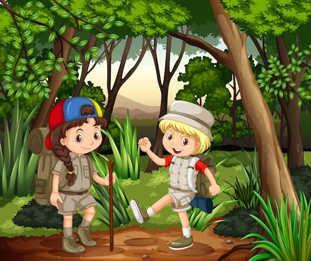 Niño y niña acampando en el bosque vector gratuito