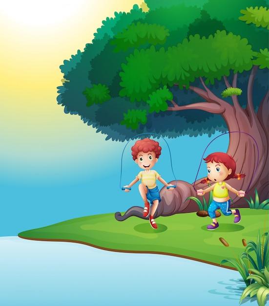 Un niño y una niña jugando cerca del árbol gigante. vector gratuito