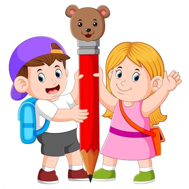 El niño y la niña sostienen el gran lápiz. | Vector Premium