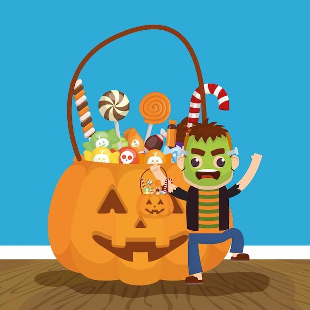 Niño pequeño con disfraz de frankenstein y caramelos de calabaza vector gratuito