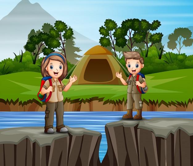 Niños acampando junto al río Vector Premium