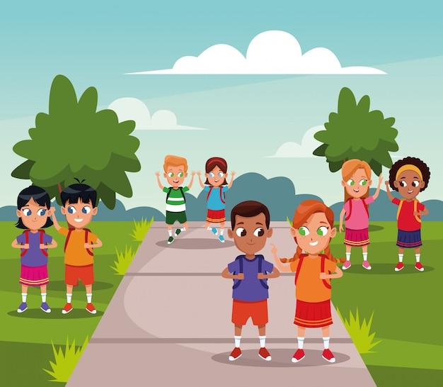 Niños de la escuela con mochila en el parque vector gratuito