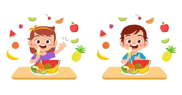 Los niños felices lindos comen frutas vegetales de ensalada Vector Premium