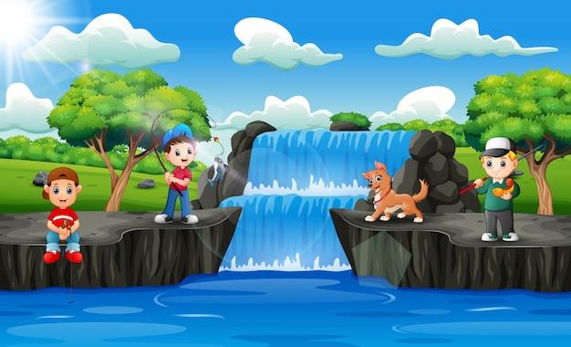 Niños felices pescando en escena de cascada Vector Premium