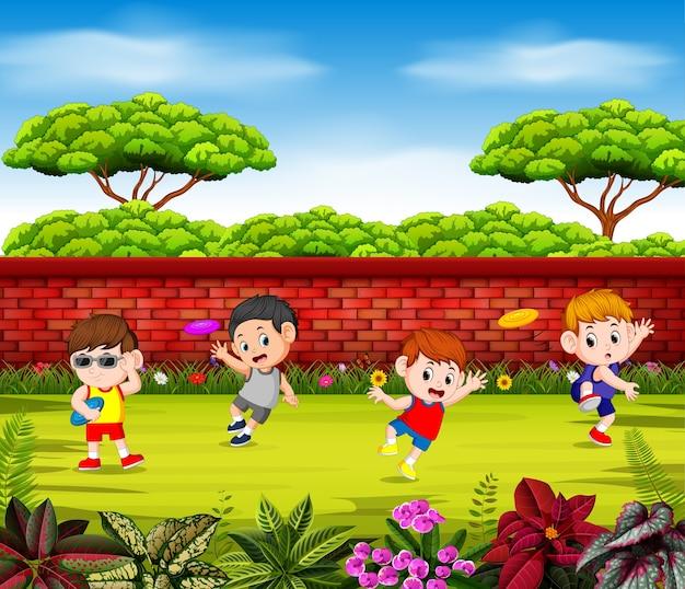 Los niños juegan al frisbee y saltan cerca de la pared roja. Vector Premium