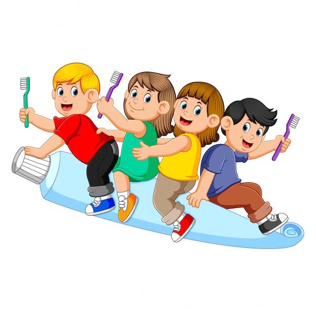 Niños montando pasta de dientes grandes y sosteniendo el cepillo de dientes Vector Premium