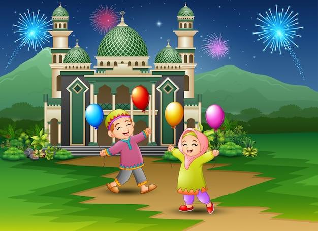 Niños musulmanes felices sosteniendo globos delante de la mezquita Vector Premium