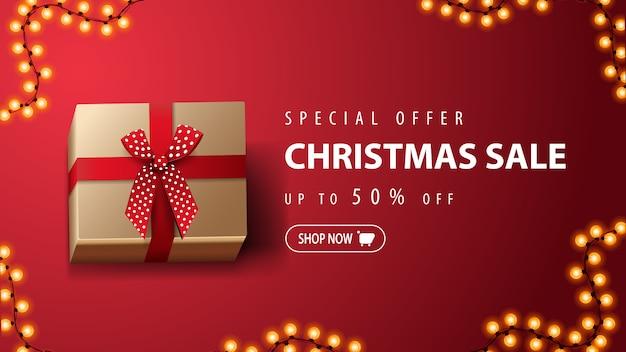 Oferta especial, venta de navidad, hasta 50% de descuento, banner de descuento rojo con regalo con lazo rojo sobre fondo rojo Vector Premium