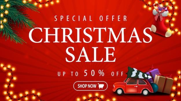 Oferta especial, venta de navidad, hasta 50% de descuento, pancarta de descuento roja con guirnalda, ramas de árboles de navidad, medias navideñas y auto rojo antiguo con árbol de navidad Vector Premium