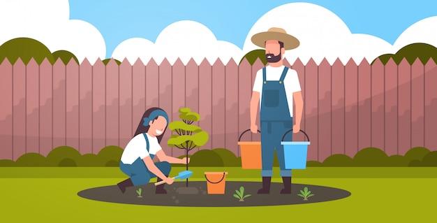 Pareja de agricultores plantando árbol joven hombre con cubos de agua mujer cavando el suelo trabajando en el jardín concepto de jardinería agrícola fondo patio plano horizontal de longitud completa Vector Premium