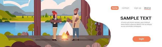 Pareja turistas excursionistas sosteniendo leña hombre mujer organizando fuego cerca de la carpa del campamento senderismo camping concepto paisaje naturaleza río montañas Vector Premium