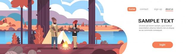 Pareja turistas excursionistas sosteniendo leña hombre mujer organizando fuego cerca de la tienda de campaña senderismo camping otoño paisaje naturaleza río montañas Vector Premium