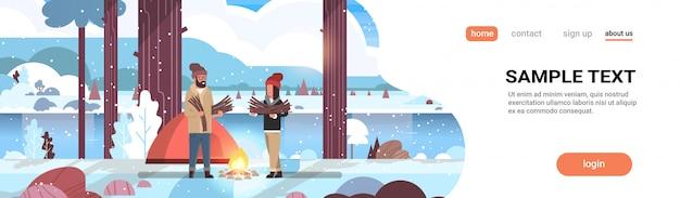 Pareja turistas excursionistas sosteniendo leña hombre mujer organizando fuego cerca de la tienda de campaña senderismo concepto de camping paisaje de invierno naturaleza río montañas Vector Premium