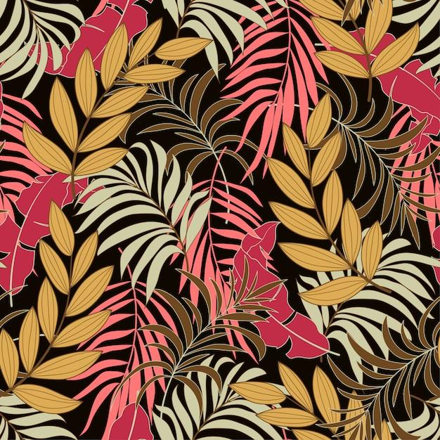 Patrones tropicales sin fisuras con plantas y hojas rojas y amarillas brillantes Vector Premium