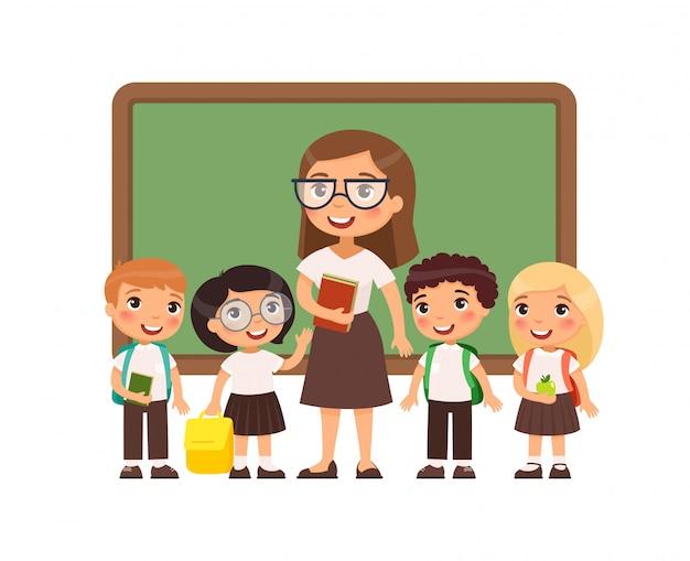 Profesor con alumnos en el aula ilustraci?n plana. ni?os y ni?as vestidos  con uniforme escolar y maestra de pie cerca de personajes de dibujos  animados de pizarra. felices estudiantes de primaria |