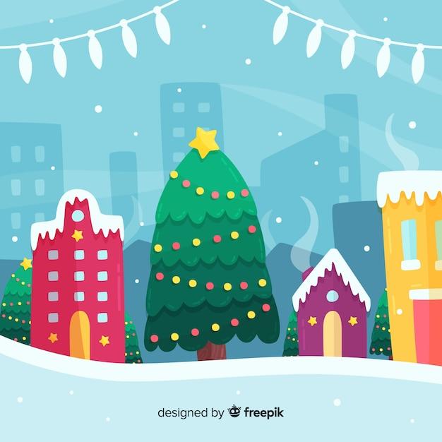Pueblo navideño con árbol en diseño plano vector gratuito