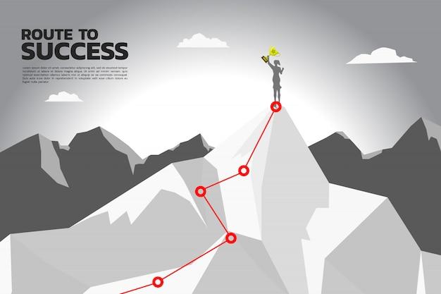 Ruta hacia el éxito. silueta de mujer de negocios con trofeo de campeón en la cima de la montaña. Vector Premium