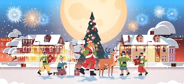 Santa mujer de pie con ciervos y mezcla de elfos de raza en máscaras año nuevo feliz navidad celebración navideña tarjeta de felicitación fuegos artificiales en el cielo nocturno paisaje urbano de fondo de longitud completa ilustración vectorial horizontal Vector Premium