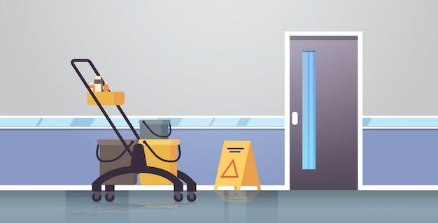 Servicio de limpieza carrito con suministros precaución signo de piso mojado empresa de conserjería moderno corredor interior Vector Premium