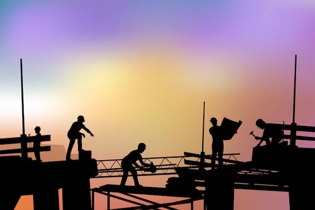 Silueta de constructores al atardecer Vector Premium