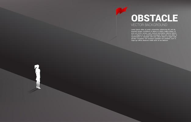 Silueta de empresaria de pie en el abismo mirando a la meta. Vector Premium