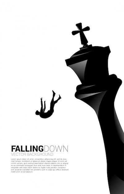 Silueta de empresario cayendo del ajedrez rey. concepto de estrategia empresarial y situación de fracaso. Vector Premium