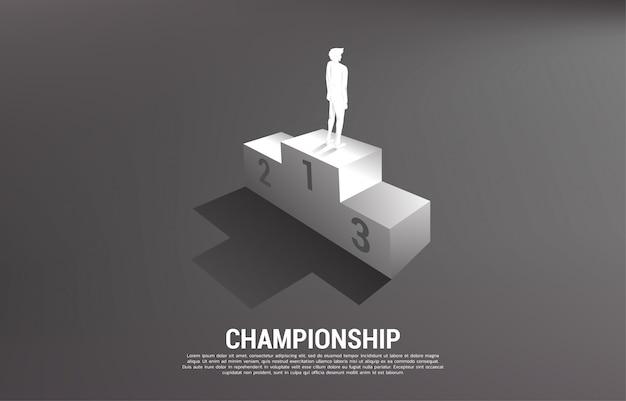 Silueta del empresario de pie en el podio del primer lugar. Vector Premium