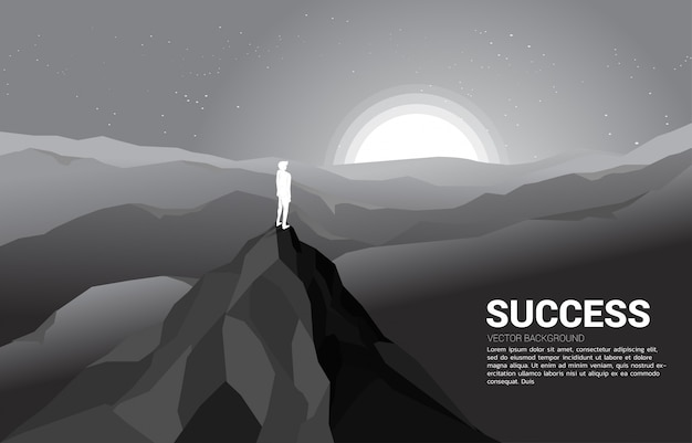 Silueta de un hombre de negocios en la cima de la montaña Vector Premium