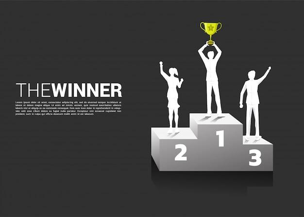 Silueta del hombre de negocios y de la empresaria con el trofeo del campeón en el podio. Vector Premium