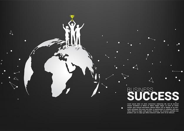 Silueta del hombre de negocios y de la empresaria con el trofeo del campeón que se coloca en mapa del mundo Vector Premium