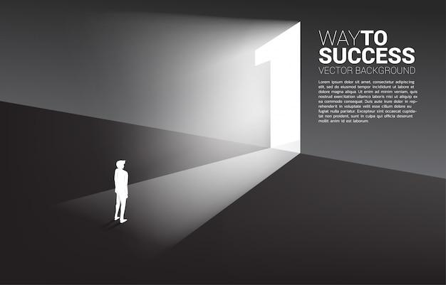 Silueta del hombre de negocios de pie delante de la puerta de salida número uno. Vector Premium