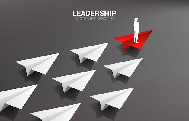 Silueta del hombre de negocios que se coloca en el grupo principal blanco del aeroplano de papel rojo del origami. concepto de negocio de liderazgo y misión de visión. Vector Premium