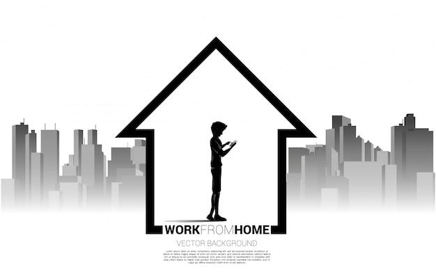 La silueta del hombre utiliza el teléfono móvil en casa con el fondo de la ciudad. concepto para trabajo remoto desde casa y tecnología. Vector Premium