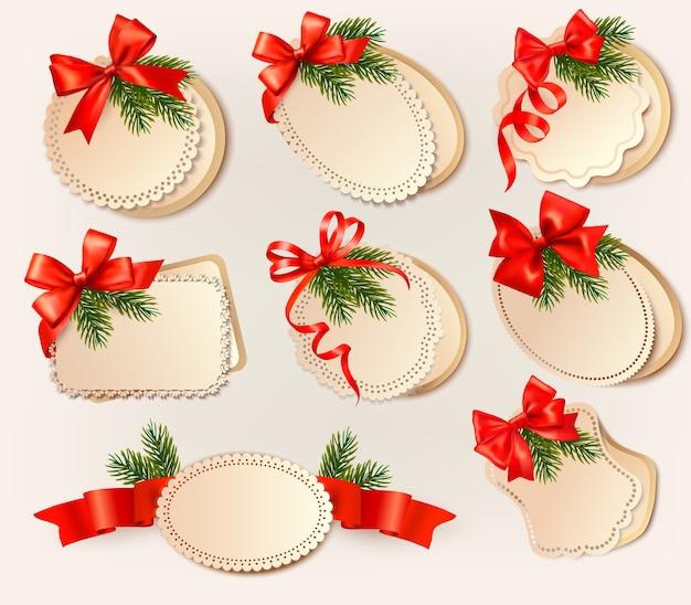 Tarjeta de navidad con lazo y ramas de árboles de navidad. Vector Premium
