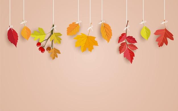 Tarjeta rosa con hojas de otoño colgando de un hilo Vector Premium