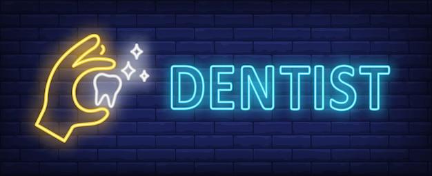 Texto de neón del dentista con la mano que sostiene el diente que brilla intensamente vector gratuito