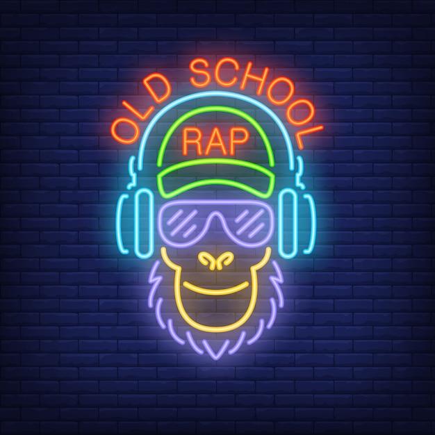 Texto de neón del rap de la vieja escuela y mono fresco en vidrios y auriculares. vector gratuito