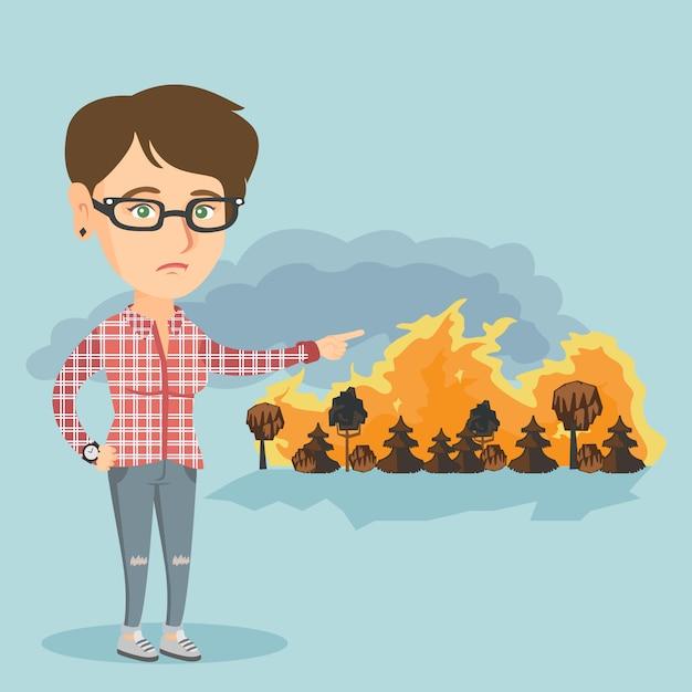 Triste mujer apuntando a incendios forestales. Vector Premium