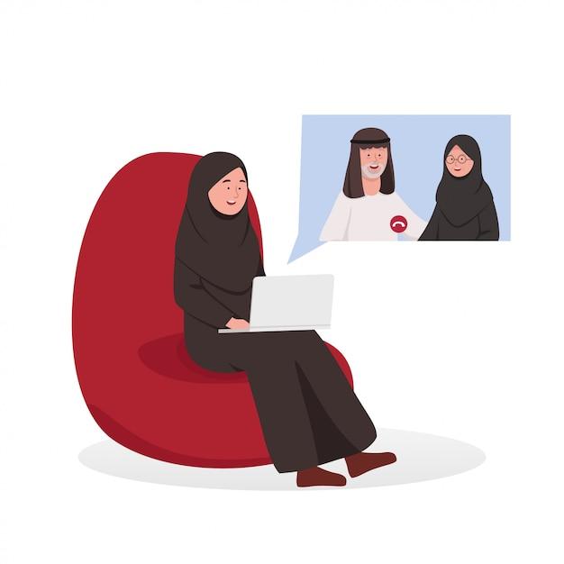 Video de mujer árabe llamando a los padres en el sofá Vector Premium