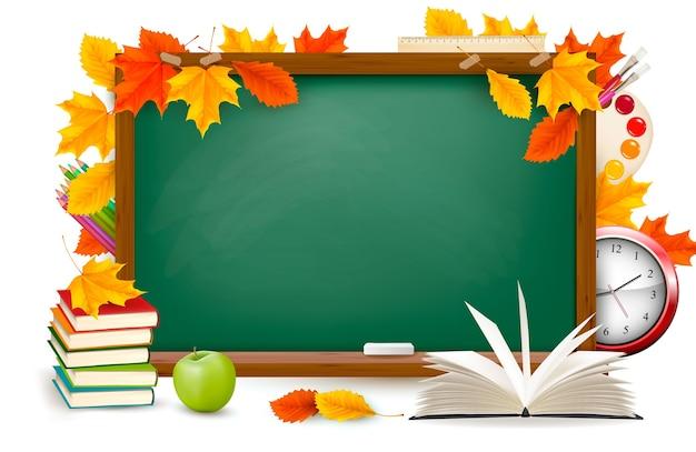 De vuelta a la escuela. escritorio verde con útiles escolares y hojas de otoño. . Vector Premium