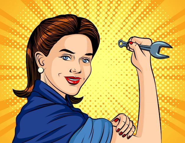 Abbildung im pop-art-stil. die frau mit einem schraubenschlüssel in der hand. internationaler tag der arbeit. schöne frau in einer arbeitsform hält den schlüssel Premium Vektoren