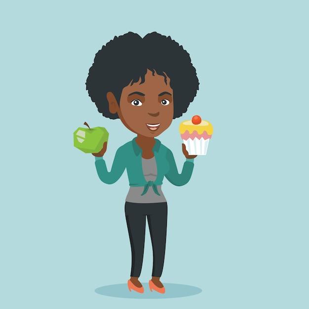 Afrikanerin, die zwischen apfel und kleinem kuchen wählt. Premium Vektoren