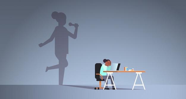 Afroamerikanerfrau, die am arbeitsplatz mit laptop sitzt Premium Vektoren