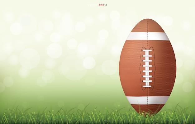 Amerikanischer fußballball auf grünem rasenfeld mit leichtem unscharfem bokehhintergrund Premium Vektoren