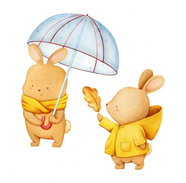 Aquarellillustration eines netten hasen im gelben schal, der einen regenschirm und ein hasemädchen in einem mantel mit einem herbstblatt hält Premium Vektoren